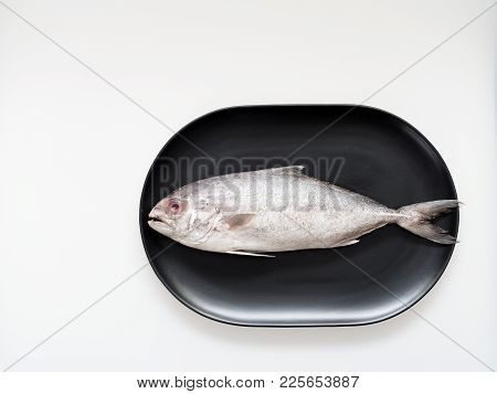 Raw Knitted Black-banded Trevally Fish On Black Oval Shape Plate Isolated On White Background