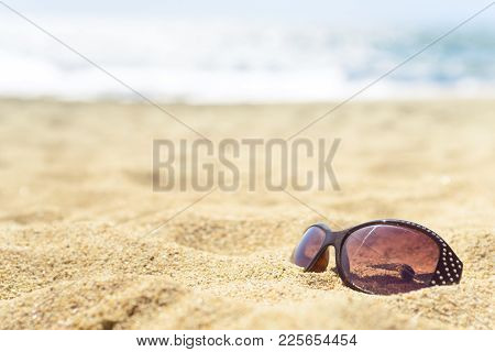 Close Up Sunglasses On The Beach On Warm Yellow Sand, With Luring Water Sparkling On Blurred Backgro