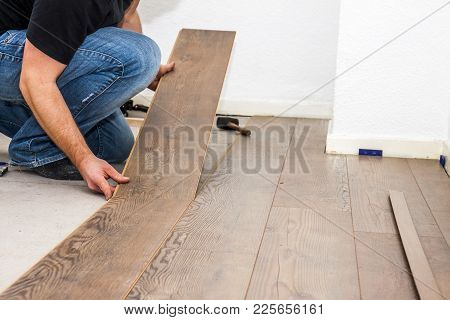 Man Removing Laminate On The Floor In Socks