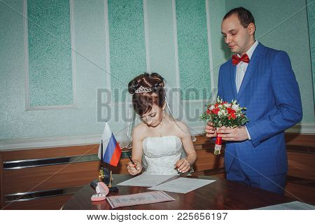 Kirov, Russia - November 24, 2017: Bride And Groom Signing Marriage Wedding Certificate At Registry