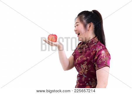 Portrait Of Asian Woman In Traditional Chinese Long Dress, Cheongsam, Presenting Apple On Hand For H