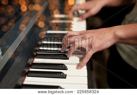 music, people, art, musical instruments and entertainment concept - close up of hands playing piano
