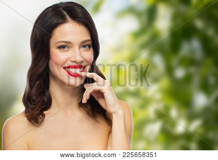 beauty, organic, make up and people concept - happy smiling young woman with red lipstick posing over green natural background