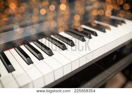 music, art, musical instruments and entertainment concept - close up of grand piano keyboard over festive lights