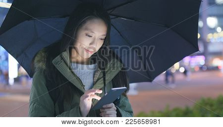 Woman use of cellphone in city with bring umbrella