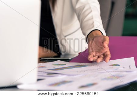 Hand Of Businesswoman Writing On Paper With Pointing On Documents In The Office Interrior