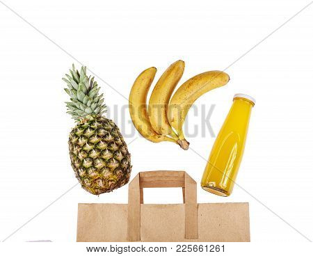 A Paper Bag With Exotic Fruits And Fruit Juice. Pineapple, Bananas And A Bottle Of Juice On A White