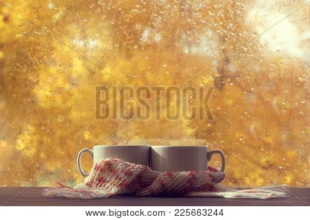 Two White Cups In Pink Scarf On Table In Front Of Window With Raindrops Autumn / Warming Hot Drink T