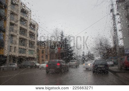 Road View Through Car Window With Rain Drops, Driving In Rain. Drops Of Rain On Glass Background. St