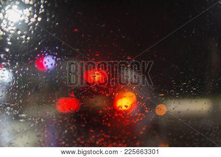 Rain Drops On Car Glass. Rain Drops On Window, Rainy Weather,rain Background. Blurry Car Silhouette.