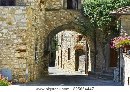 Narrow Passage Between Old Houses In Italy. Street With Archway In The Medieval Italian Town.