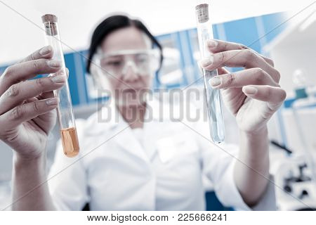 Let Me See. Selective Focus On Two Test Tubes Containing Chemical Liquids Held By A Mature Lady In A
