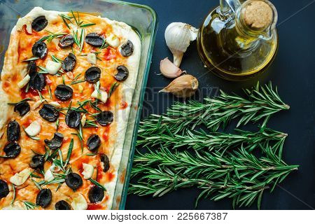 Home Focaccia With Olives And Rosemary On A Black Table Top View. The Process Of Cooking Italian Bre
