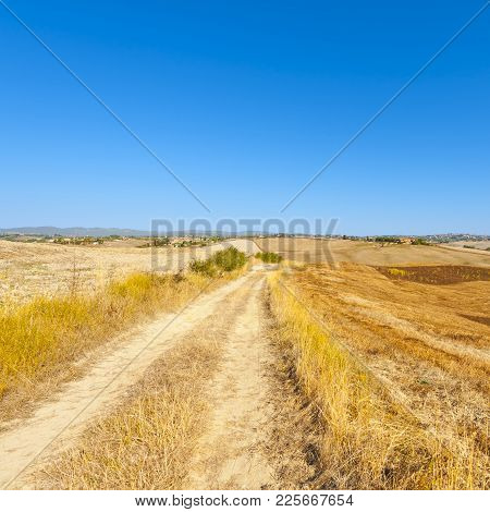 Stubble Fields On The Hills Of Tuscany. Tuscany Landscape After Harvest. Dirt Road Between Plowed Fi