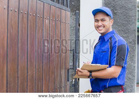 Smiling Techinician In Blue Uniform Coming To Customer House