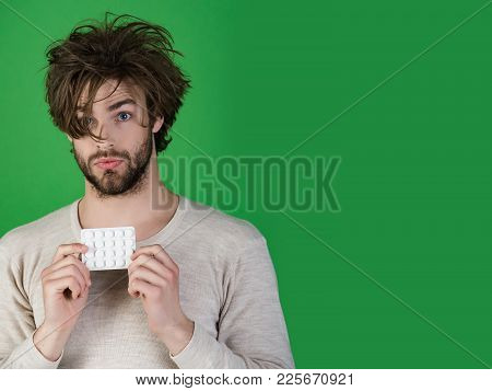 Man With Pills In Blister Pack Has Uncombed Hair In Morning On Green Background, Health And Medicine
