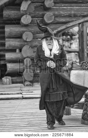 Old Man Wizard With Long Grey Hair Beard In Black Costume And Hat For Halloween Outdoors On Log Hous