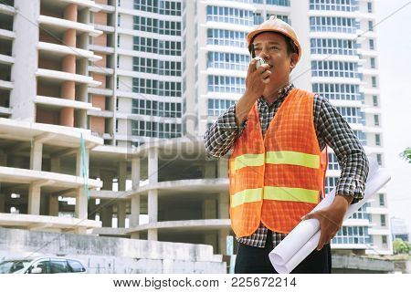Contractor With Blueprint Using Walkie-talkie To Give Instructions To Employees