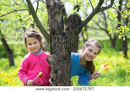 Two Lovely Girls Peeking Out From Behind The Tree And Holding Easter Eggs. Hunting For Easter Eggs
