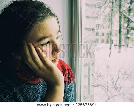 Sad teen girl looks out the window