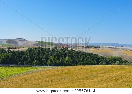 Plowed Sloping Hills Of Tuscany In The Autumn. Rural Landscape With Field After Harvest. Asphalt Roa