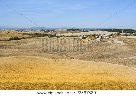 A Barn With Bales Of Wheat Hay In Italy. Plowed Sloping Hills Of Tuscany In The Autumn. Rural Landsc