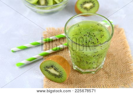 Sliced Kiwi And Smoothie Slices In A Glass On A Gray Table. Healthy Food
