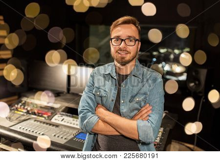 music, technology, people and equipment concept - happy smiling man at mixing console in sound recording studio over festive lights