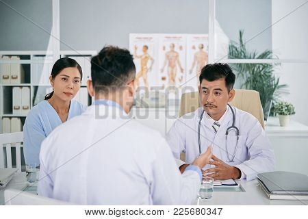 Doctor Conducting Meeting With His Coworkers In Office