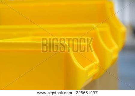 Close Up Of Yellow Plastic Parts Bins. Space For Text. Shallow Depth Of Field.