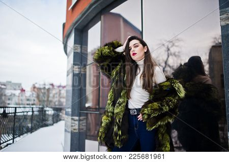 Brunette Girl In Green Fur Coat At Street Of City Against House With Large Windows At Winter.