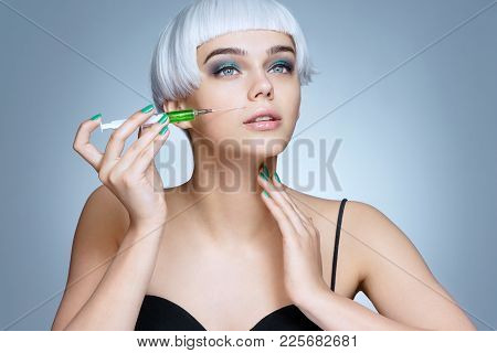 Beautiful Woman Face With Syringe Making Rejuvenate Injection. Clean Beauty Concept