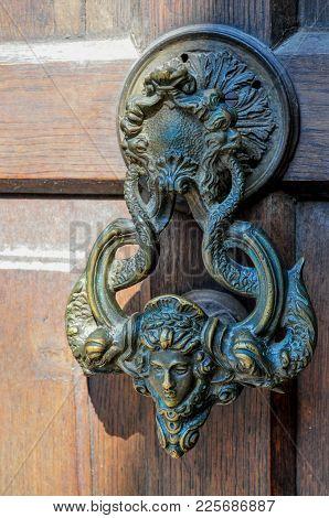 An Ancient Door Knocker On A Wooden Door