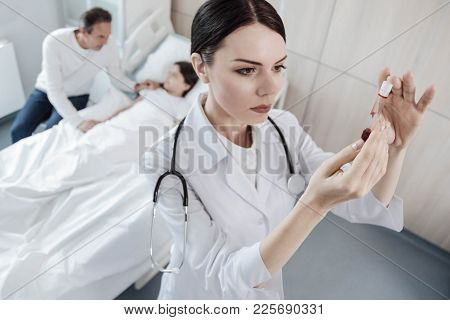 Attentive Examination. Selective Focus On A Concentrated Female Medical Worker Examining A Test Tube