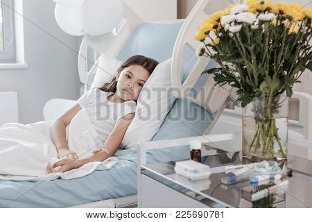 Tired And Exhausted. Adorable Ill Girl Looking Into The Camera With Eyes Full Of Sadness While Lying