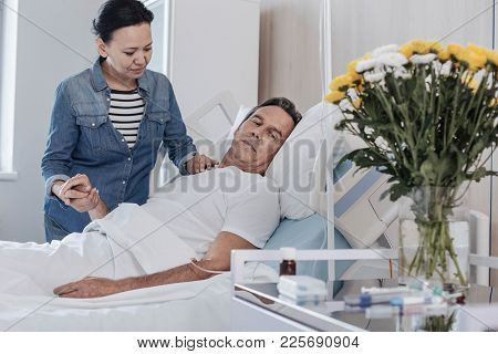 Everything Will Be Good My Love. Mindful Mature Lady Holding Hand Of Her Husband While He Lying In A