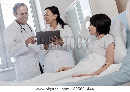 Promising Result. Low Angle Shot Of A Team Of Doctors Looking Satisfied While Looking At The Result