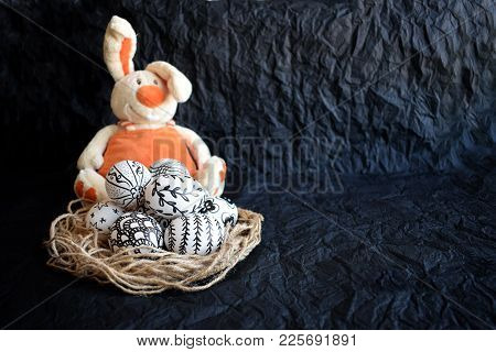 Easter Eggs With The Hand-drawn Different Doodle Patterns And Cute Orange Toy Rabbit On A Black Back
