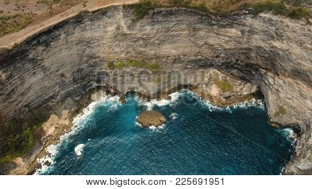 Cliff With Waves Crashing Against A Rocky Shore, Nusa Penida, Indonesia. Aerial View Rocky Shore And
