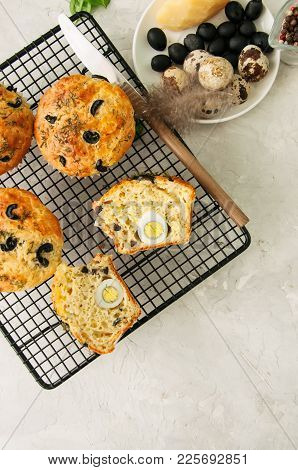 Savory Muffins With Olives, Quail Eggs And Herbs On A Wire Rack On A White Stone Backdrop. Rustic St