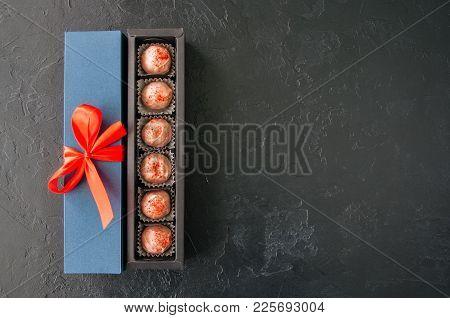 Blue Gift Box With Red Tape With Chocolate On A Black Stone Background