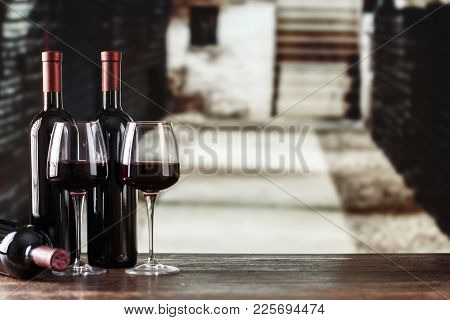 Red Wine In Glasses On The Background Of The Cellar, In The Wine Cellar Wine Is Located On The Shelv