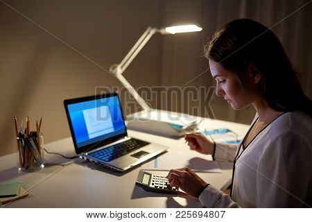 business, accounting, overwork, deadline and people concept - woman with tax form and calculator working at night office