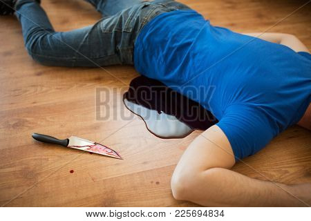 murder, kill and people concept - dead man body and knife in blood lying on floor at crime scene (staged photo)