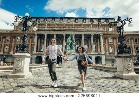 Full-length View Of The Pretty Young Couple In Love Holding Hands While Walking Along The Countryard