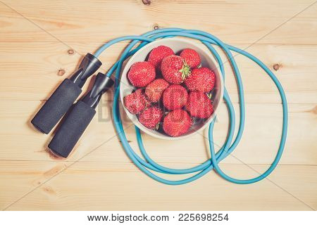 Skipping Rope And Bowl Of Fresh Strawberry On Wooden Background. Top View.