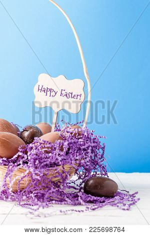 Image Of Chicken, Chocolate Eggs, Purple Decorative Paper In Basket On Empty Blue Background With Wi