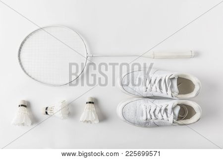 Top View Of Badminton Racket With Suttercocks In Row And Sneakers On White Surface