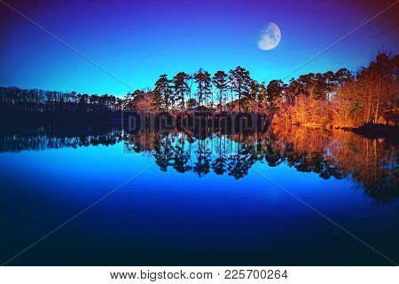 A Sultry Blue Lake Lined With Dramatic Trees Reflecting In The  Water.
