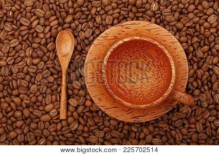 Empty Brown Coconut Palm Carved Wood Coffee Cup On Wooden Saucer And Spoon Over Background Of Roaste